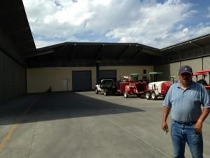 Yuan Martinez standing in front of the winery equipment