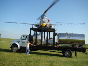 Helicopter's stop to refuel and reload product from a large tanker truck.