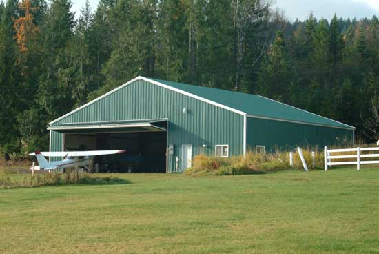 Farm building with a bifold hanger door for aircraft storage