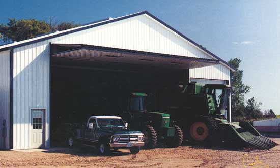 Farm building storing farm equipment with bifold door