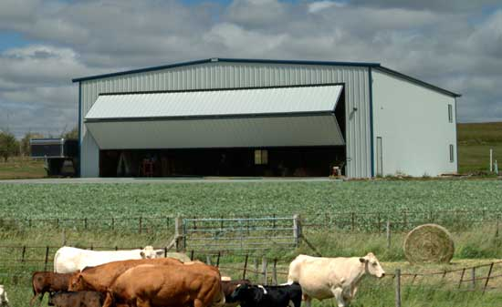 Farm building equipped with a bifold door, housing farm equipment