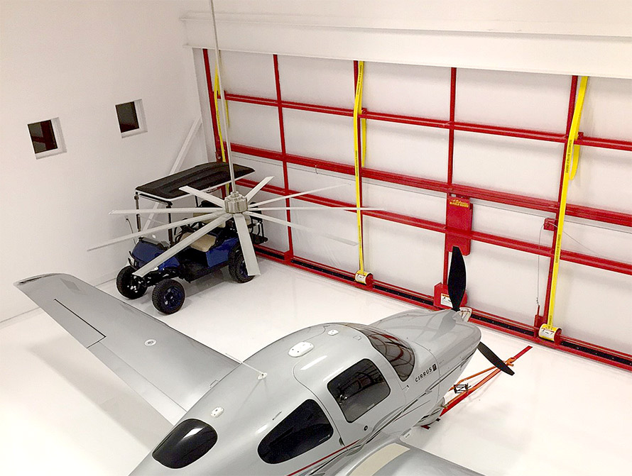 beautiful hangar with schweiss door holding Cirrus plane