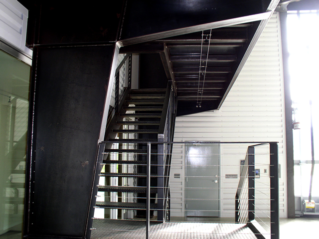 metal stairway in hangar with glass bifold door