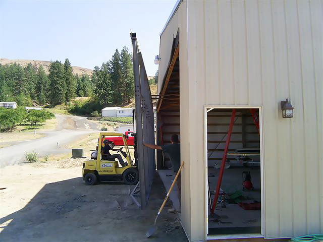 moving hydraulic door into place on building for installation