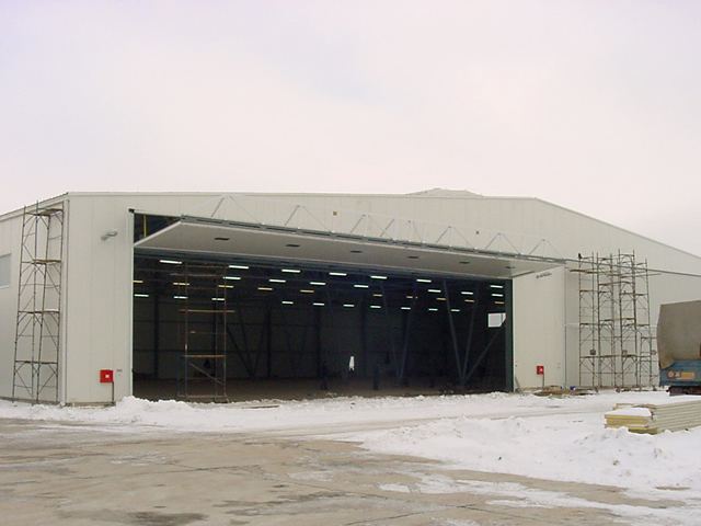 large bifold door fully opened on european aircraft hangar