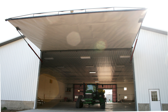 Large hydraulic door opens farm machine shed