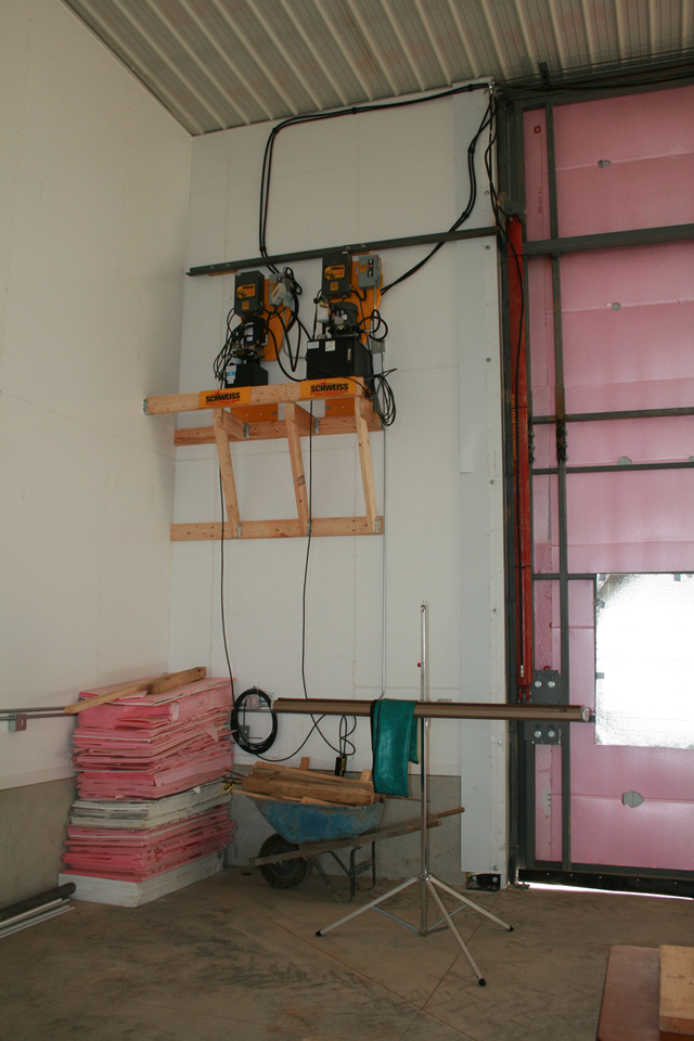 Twin hydraulic door pumps mounted high on wall
