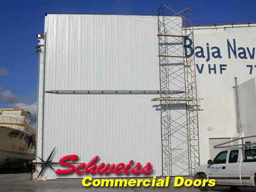 Tall Industrial Bifold Door with Sheeting at a Dockyard