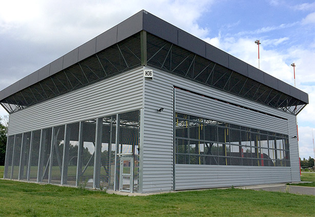 Belgian Airforce military Helicopter Hangar is clad in mesh for ventailation on two 64' x 23' straplift/autolatch doors
