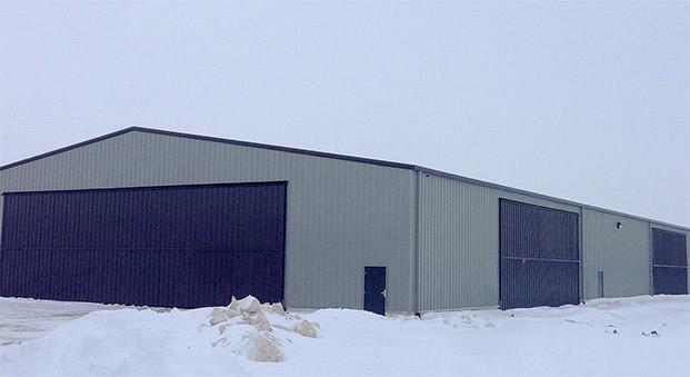 steel building with Schweiss bifold liftstrap doors -- 60 by 18 and 40 by 16