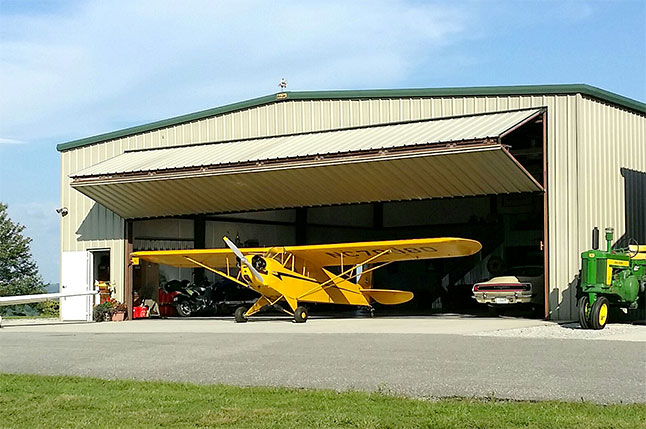 Larry Robbins of TN has his planes outside of 44'x 14.5' Schweiss bifold liftstrap door