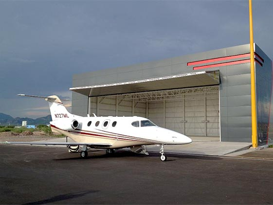 Schweiss Bifold Autolatch/Lifstrap door easily gives Hawker Beech Craft Premier A1 access to the hangar45 foot Machine Shed Door are lifted by Four Schweiss Bifold Liftstraps