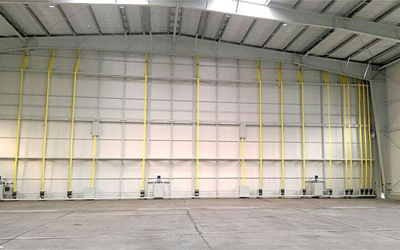 33,000 lb hangar door is raised by twelve Schweiss patented straplifts