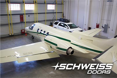 inside view of hangar with a Schweiss Bifold door with large jet