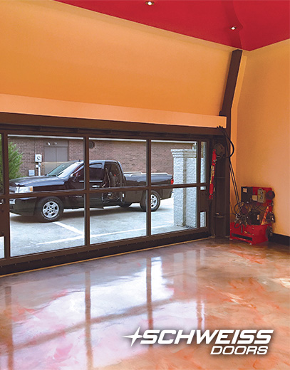 Schweiss Hydraulic door has electric photo eye sensors and a remote opener. There is also a high ceiling to add a stackable car lift inside