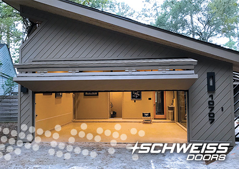 Schweiss Liftstrap bifold Garage door is clad with matching exterior to the rest garage