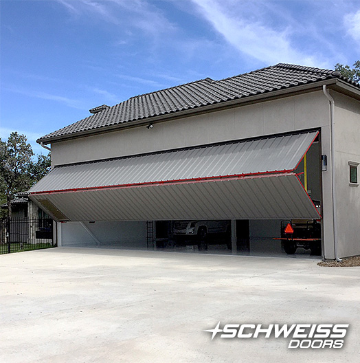 Schweiss Bifold Hangar Door with Red Frame with Man door is closing