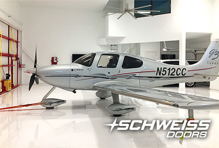 Schweiss Bifold Hangar door is closed after taxiing Cirrus to resting spot