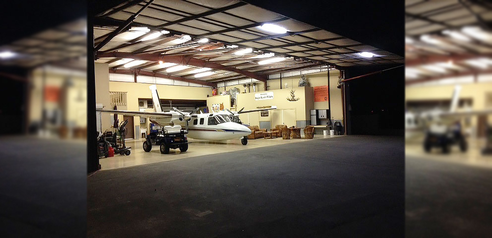 View inside the hangar, the 56x16 ft door open showing an Aero Commander Shrike