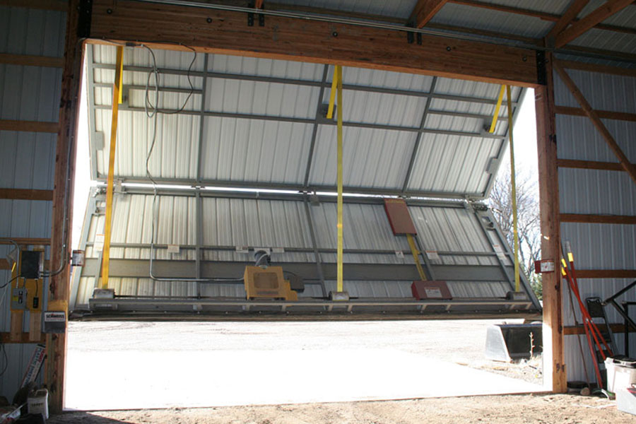 Bifold door lifts straight up to machine shed ceiling