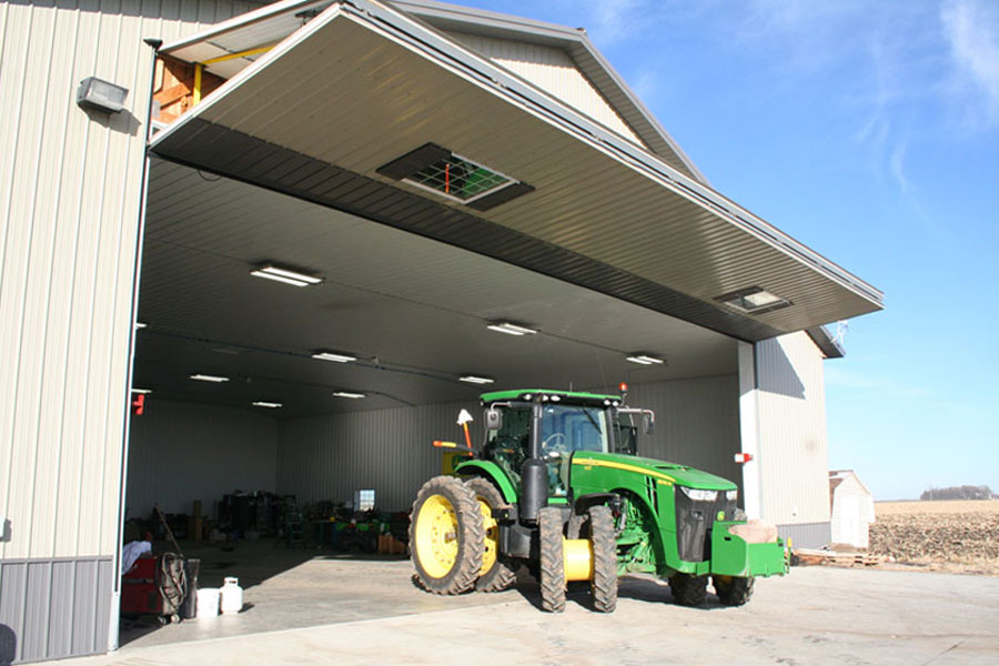 Door canopy provides shade for farm machine shed