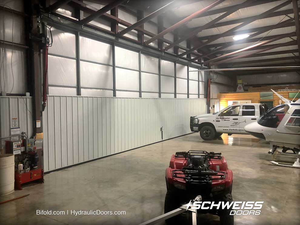 Hydraulic Hangar Door is equipped a windpin, and has multiple vehicles inside.