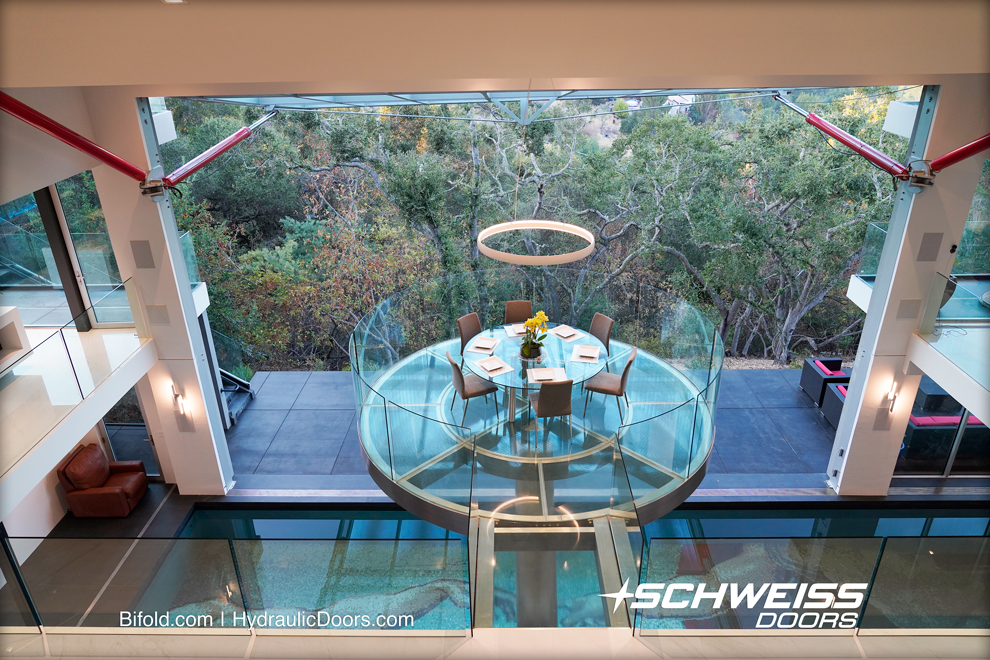 Dining Table is held above the pool and infront of Schweiss Hydraulic Door