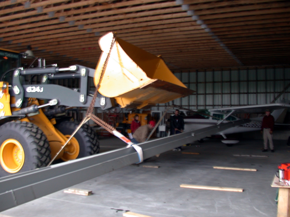 Members used a front-end loader to lift the bifold door into place