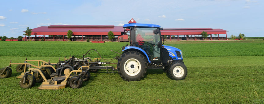 New Holland tractors are mowing the area by the door manufacturing facility