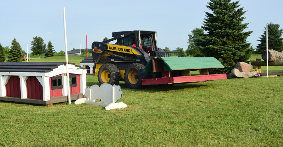 A New Holland skidloader moving a jump obsticle for the Magister Equitum Stables