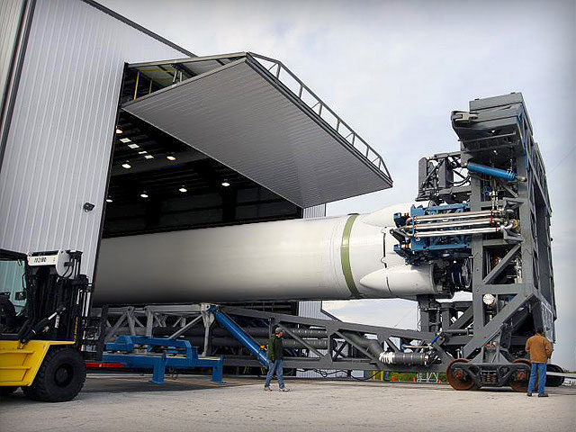 The Dragon rocket is being rolled out from underneath a bifold door