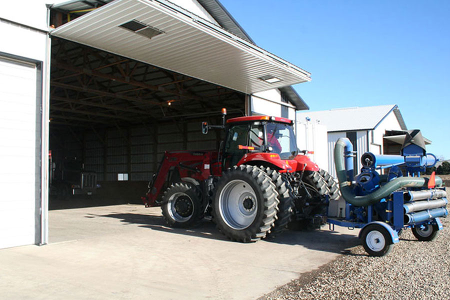 Tractor and farm equipment moving in the shed