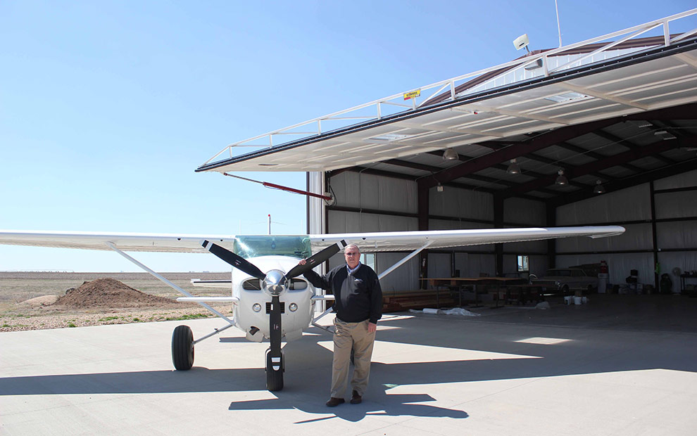 Stan Reiss with his airplane in front of a Schweiss Hydraulic Door