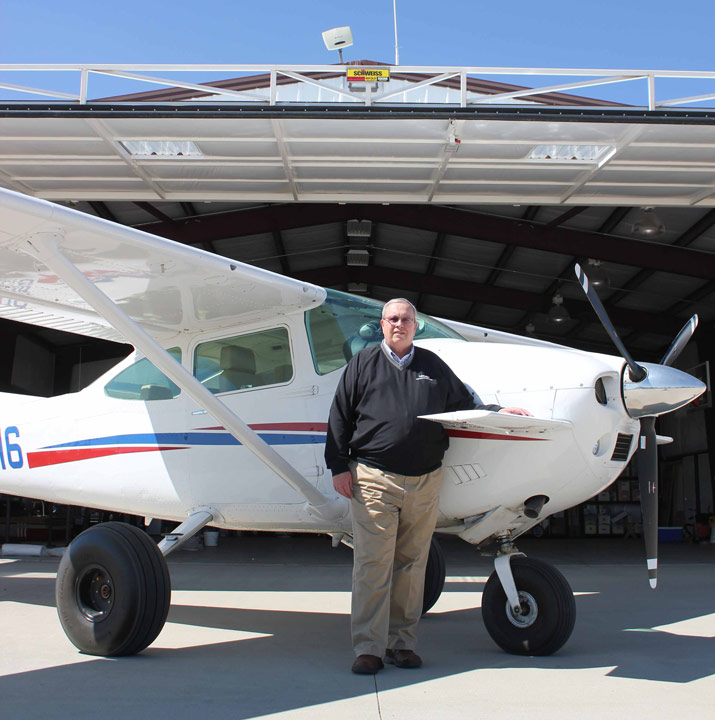 Stan and his 1979 Cessna 182 Skylane in front of his multi-functional hangar
