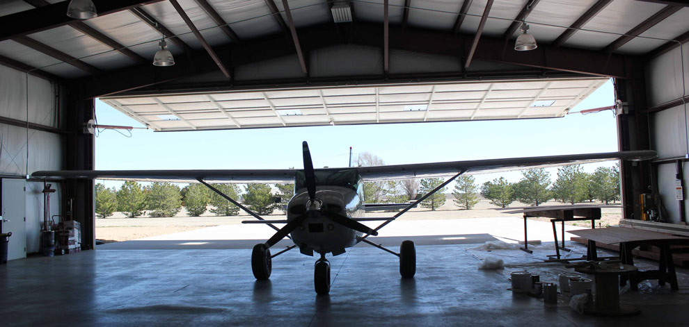 Inside the hangar seeing the open 16 foot tall hydraulic door and the shade it provides