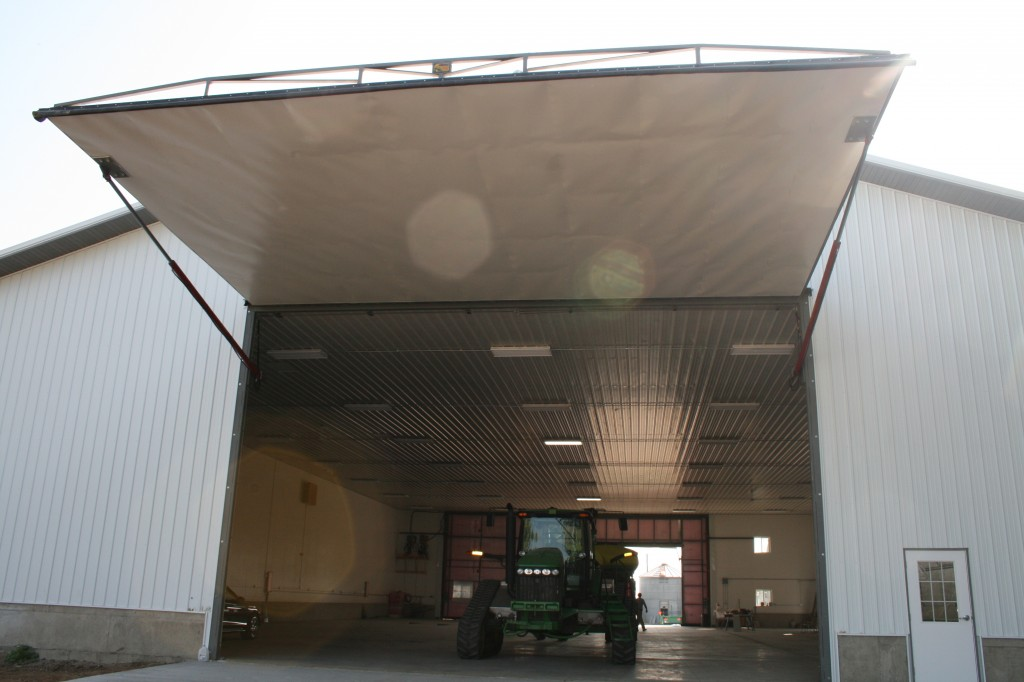 Big hydraulic one piece doors are used by farmers with large tractors and machinery. The Schweiss hydraulic doors have strong cylinders and a compact pump unit.